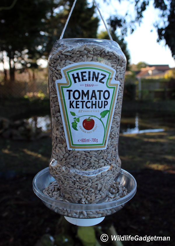 Make a hanging bird feeder using a recycled heinz tomato for Making a bird feeder out of recycled materials